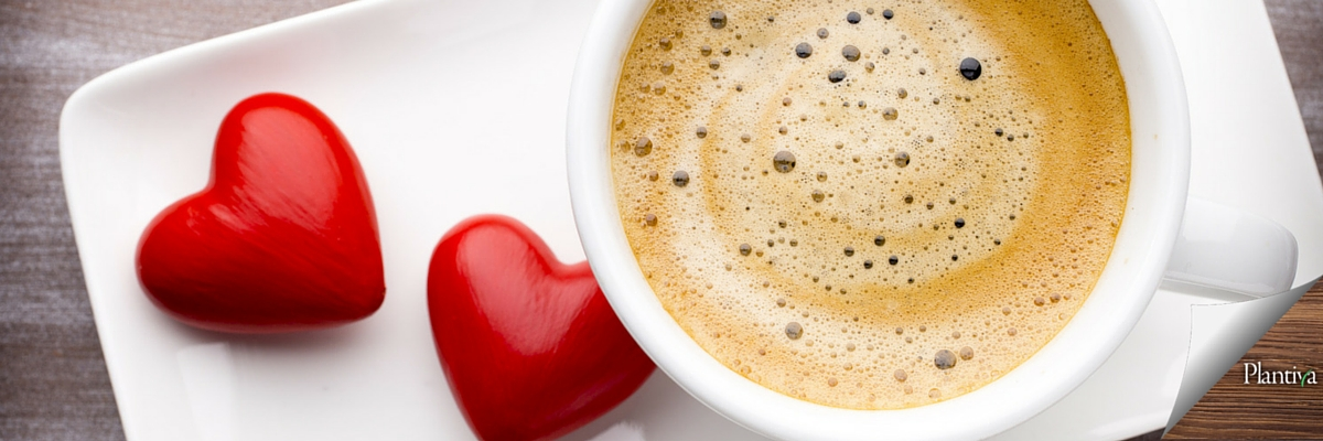 cup of coffee with cream on a plate next to two hearts